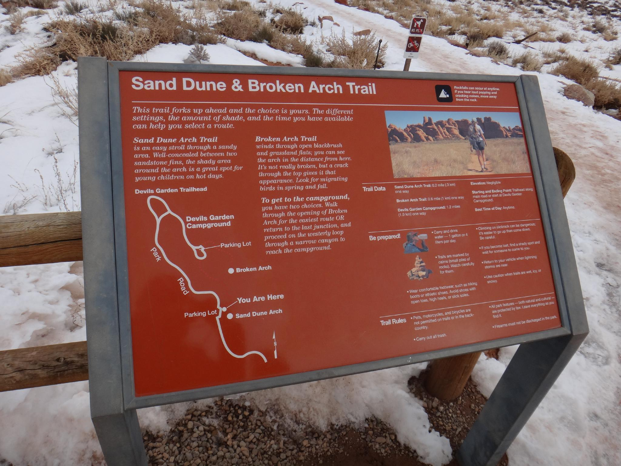 sand dune and broken arch trail information sign road trip ryan
